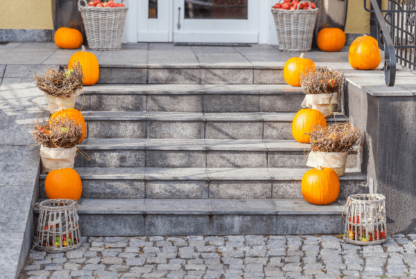 curb appeal exterior of home in fall - pumpkins on stairs