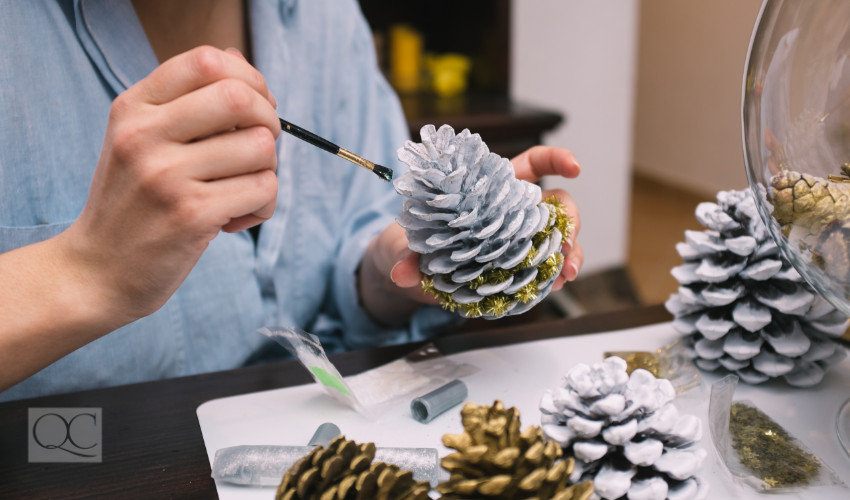 woman painting a pine cone to DIY decorate