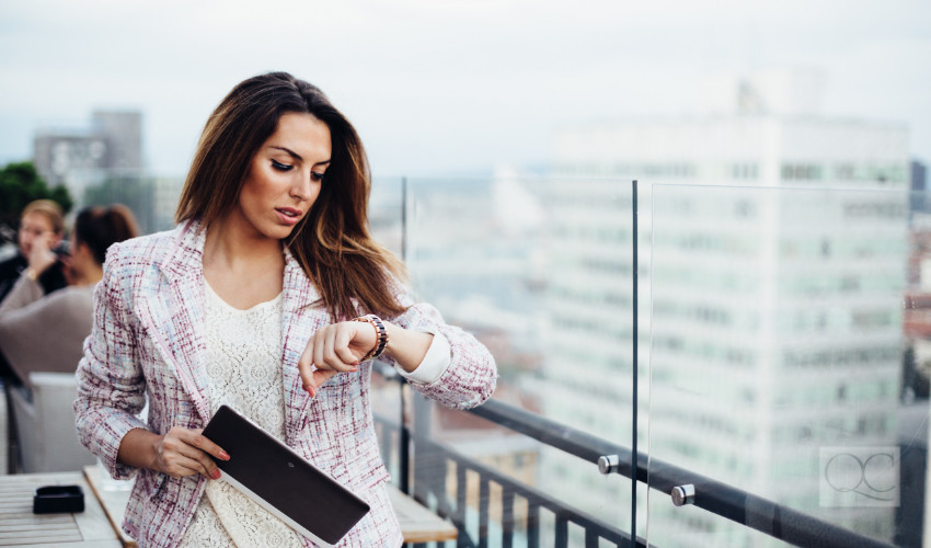 business woman checking clock to keep organized and on time