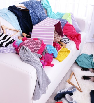 Messy couch covered in clothes