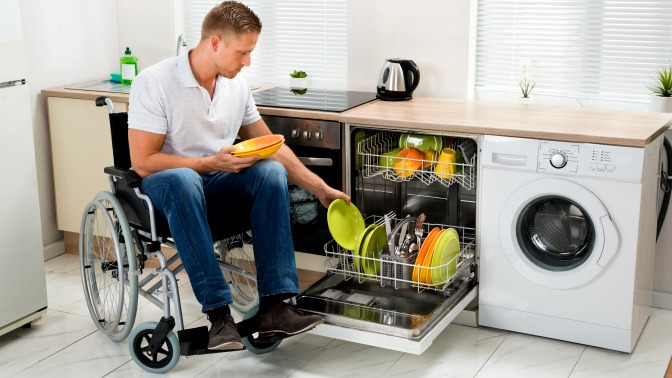Man in wheelchair loads dishwasher