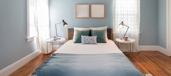 A wooden bed and a blue color scheme create a bedroom with good feng shui