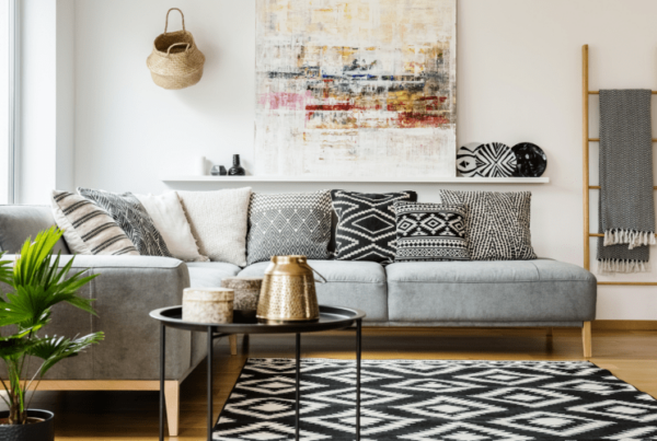 Patterned pillows on grey corner sofa in living room interior with table and painting