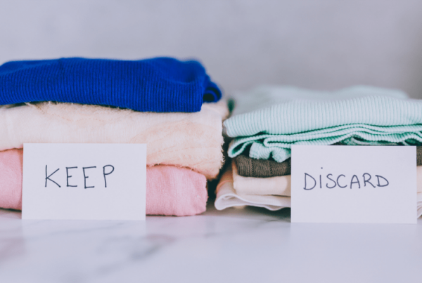 two piles of clothes side by side, sorted by keep and discard signs