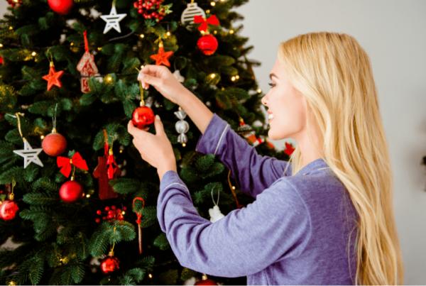 smiling woman decorates christmas tree