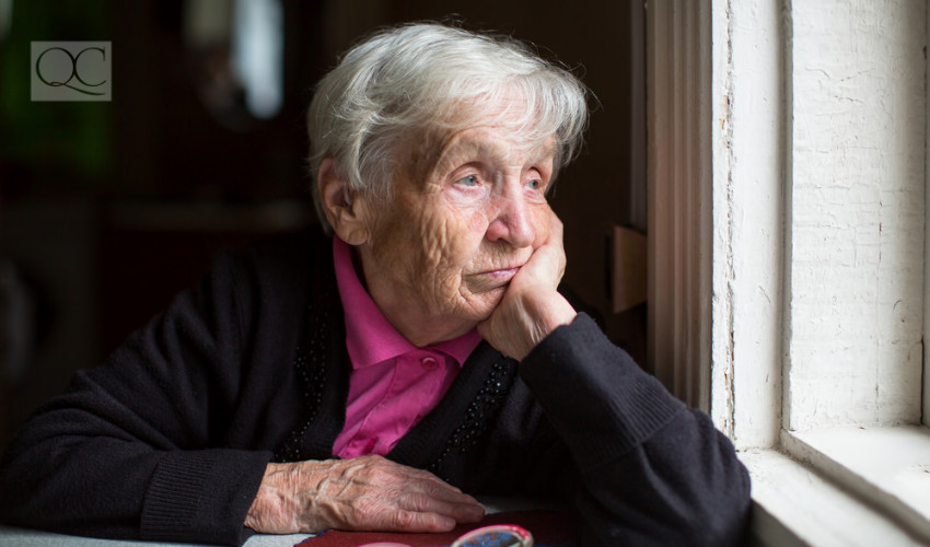 old lady looking out of window sad and pensive