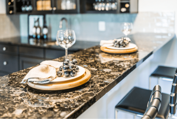 wooden plate, wine glasses, and fake grapes - home staging in kitchen