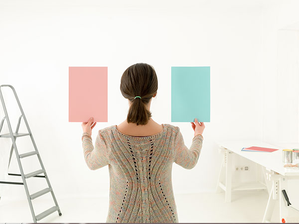 Woman deciding on color paint swatch for room