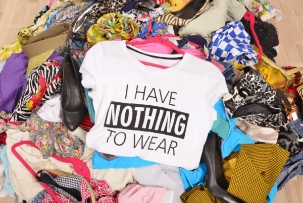 "messy pile of clothes and shoes on floor, with shirt on top that reads ""i have nothing to wear"""