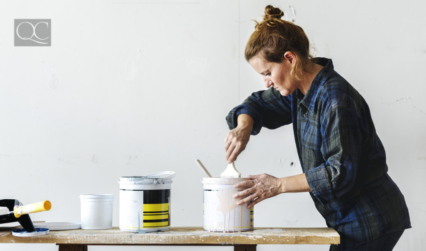 creative interior decorator getting her hands dirty with painting