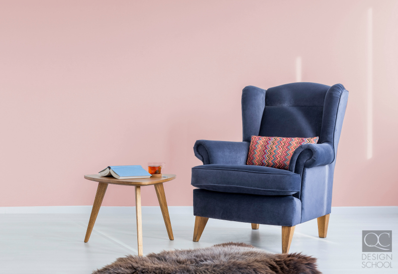 Pastel pink colored wall and blue chair.