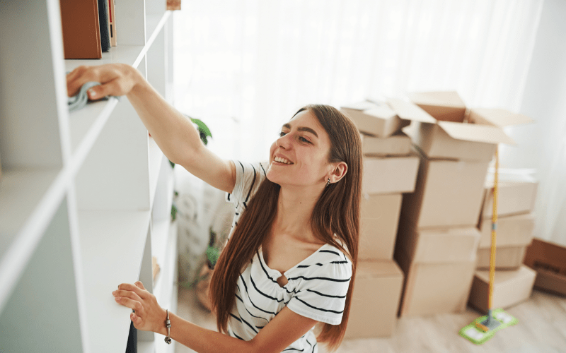 female pro organizer wiping down shelf with cloth, with packing boxes behind her