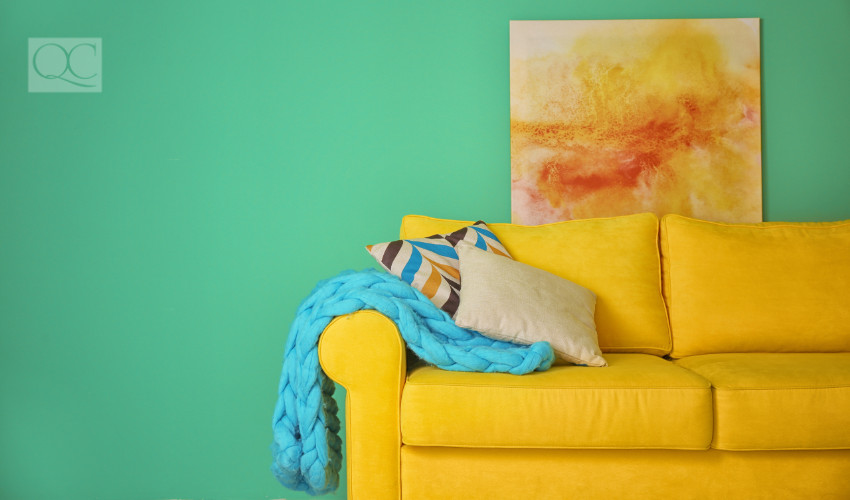 Color coordinated couch with throw blanket and painting