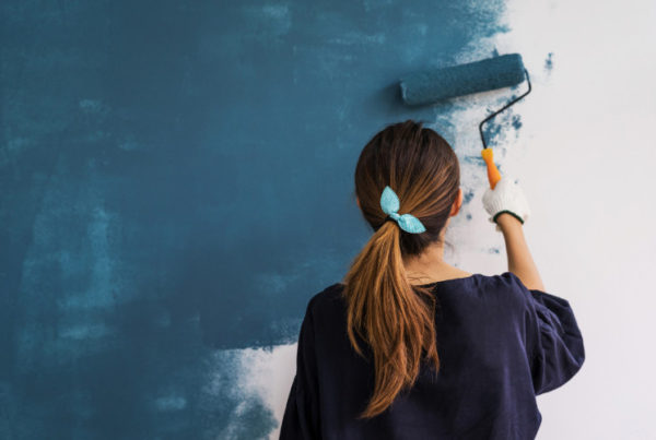 professional color consultant painting first coat of blue paint on the wall