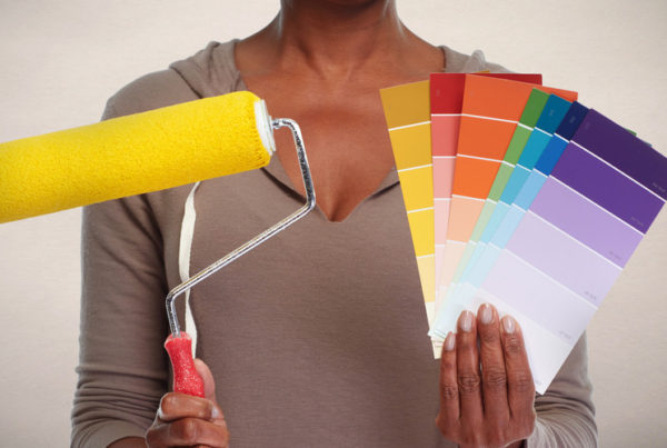 professional color consultant holding up paint swatches and a roller brush with wall paint color