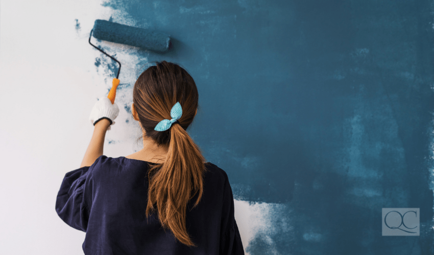 woman using roller to paint a wall a dark turquoise