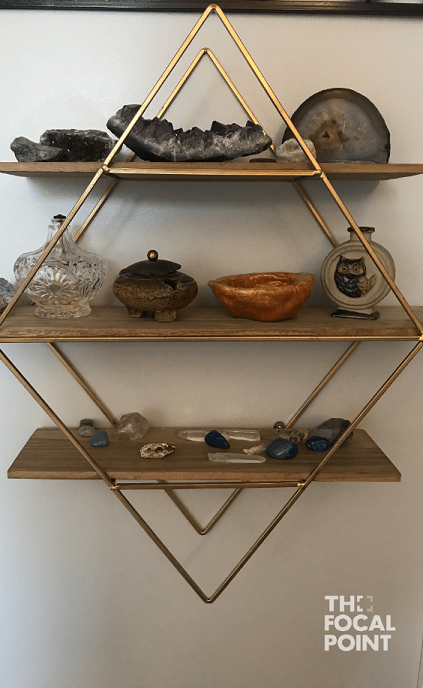 diamond-shaped open concept shelf on wall, with stones and crystals on the shelves