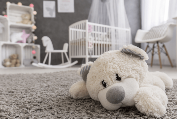 Shot of a teddy bear laying on a carpet in a cozy gender-neutral baby room