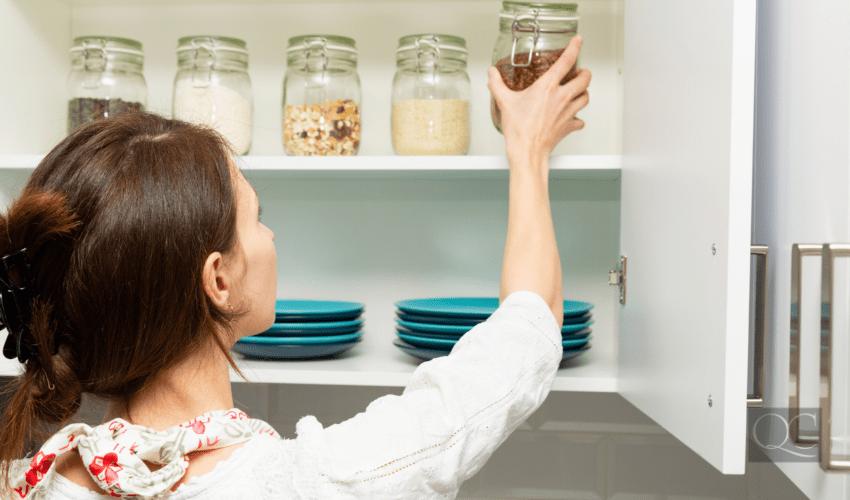 Women stacking item in storage hutch. Smart kitchen organization concept
