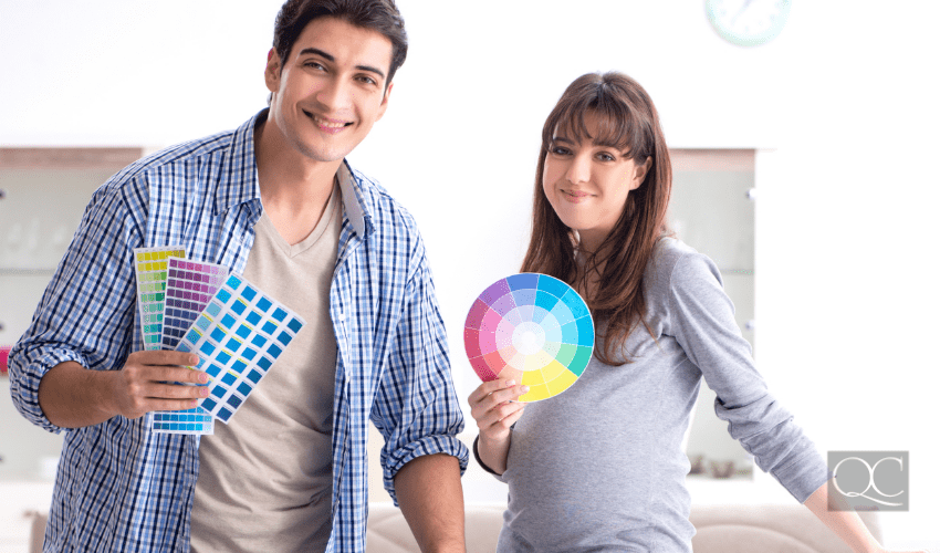 Young parents expecting their first baby, choosing colors for nursery room