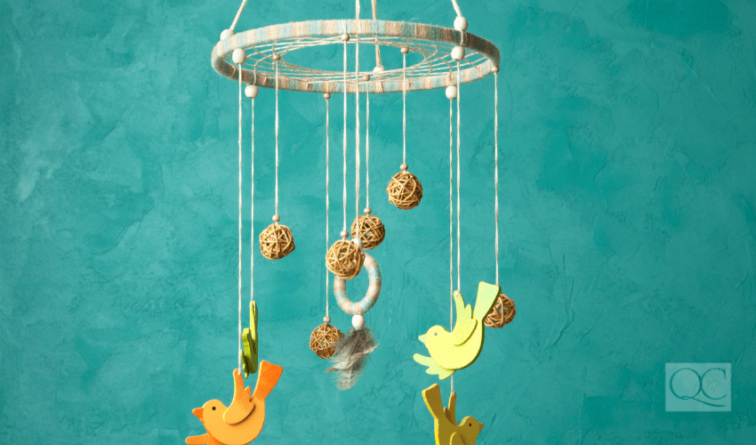Handmade multicolor baby crib mobile with rattan balls close up on turquoise background