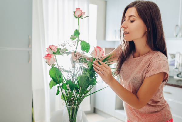 woman interior decorating - arranging flowers in vase