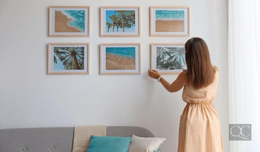 woman interior decorating - hanging framed art up on living room wall