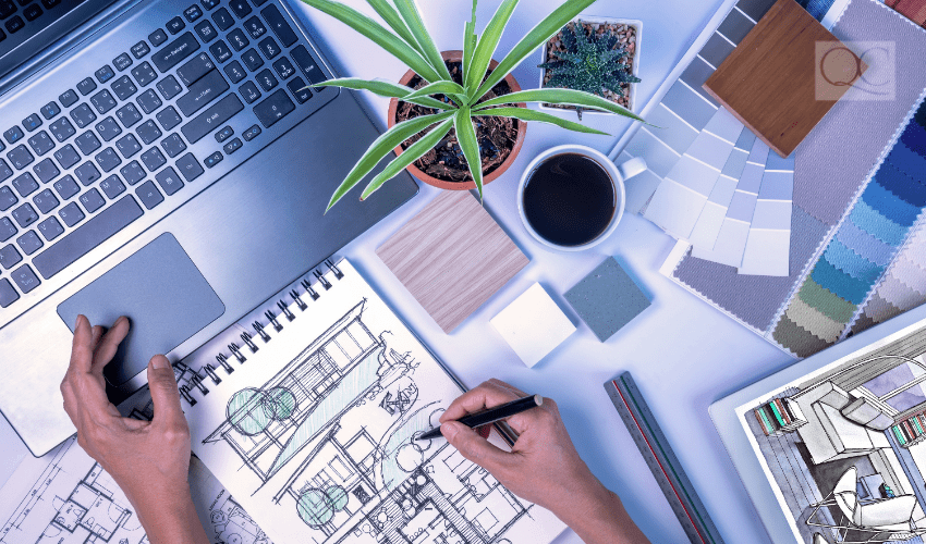 overview of interior designer working on a blueprint and laptop