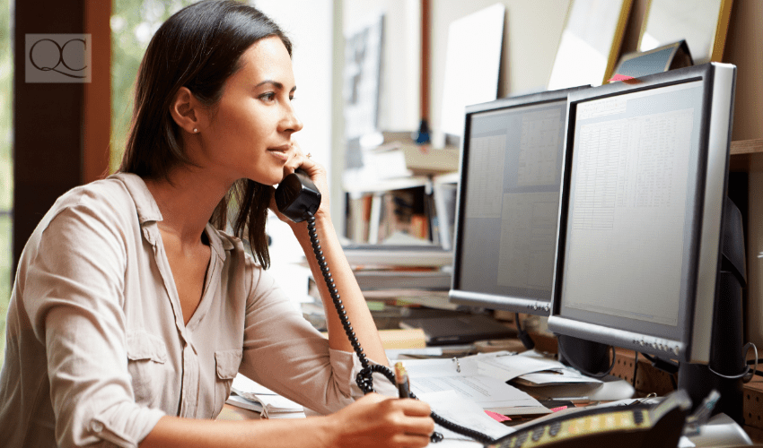professional woman working on computer and speaking on the phone
