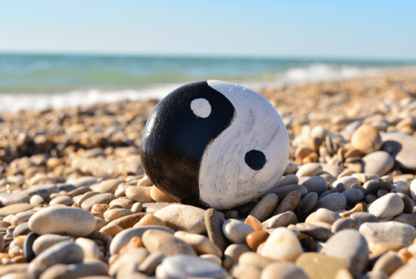 Feng Shui yin and yang symbol painted on rock on rocky beach