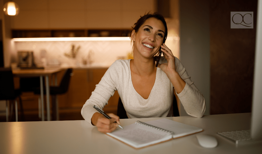 woman talking on cell phone and taking notes