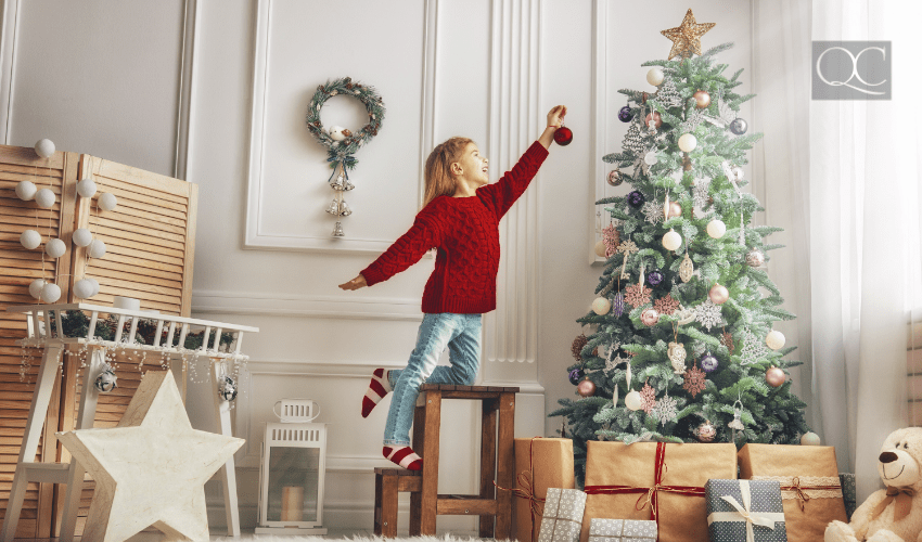 child decorating christmas tree at home
