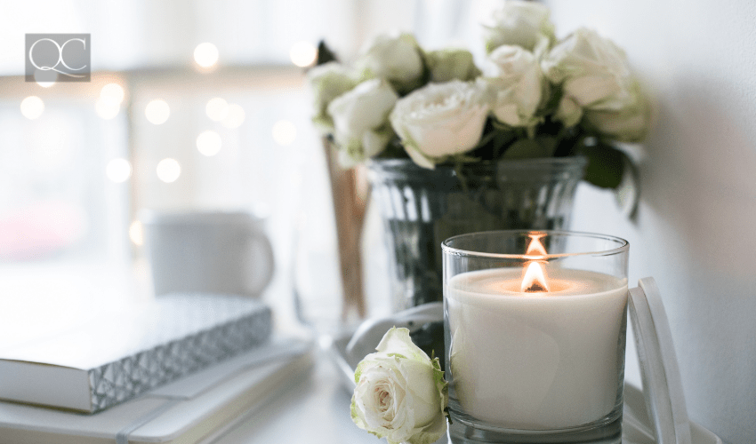 white candle burning in front of potted white roses