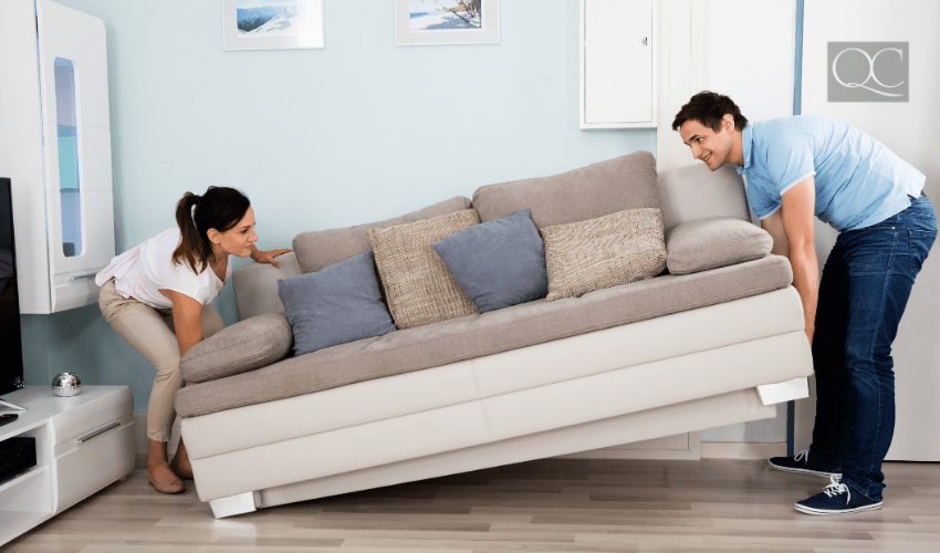 couple moving couch in living room