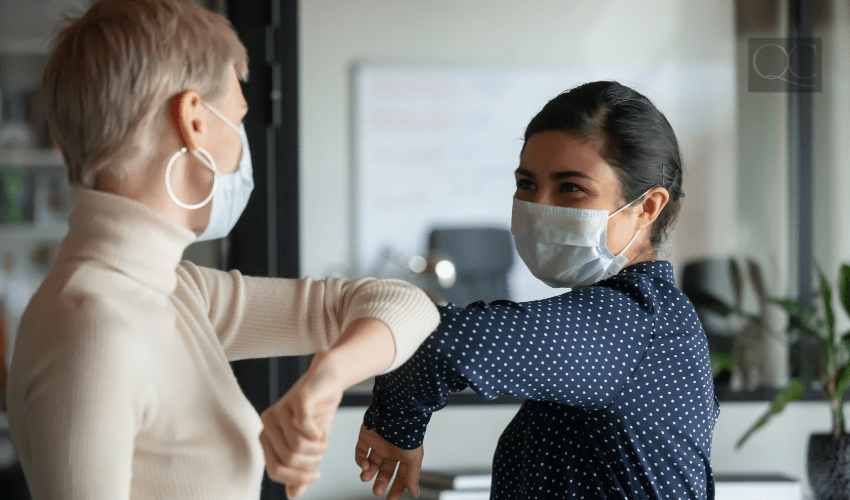 two women wearing face masks and bumping elbows to say hello
