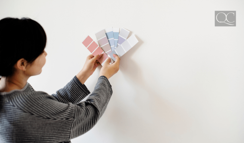 woman holding up paint color swatches to white wall
