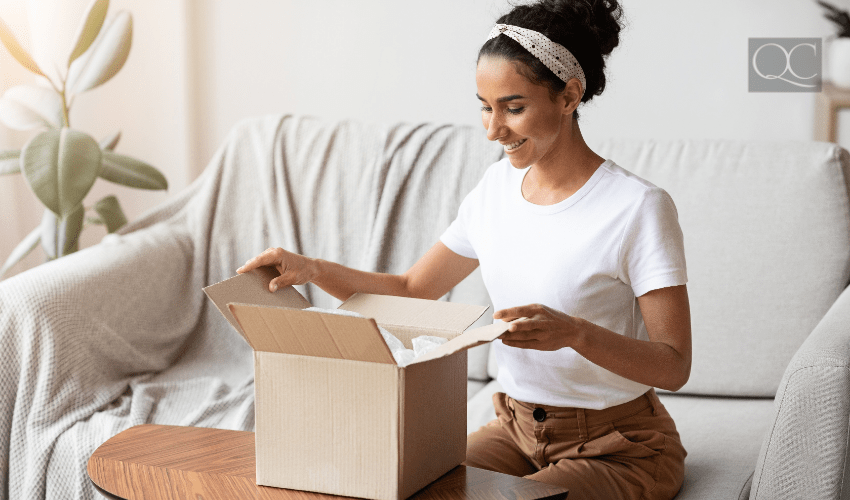woman opening package at home in living room