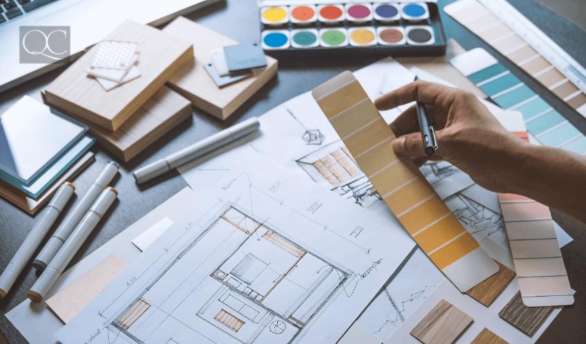 designer with floorplan, colors, paint swatches, etc. on desk