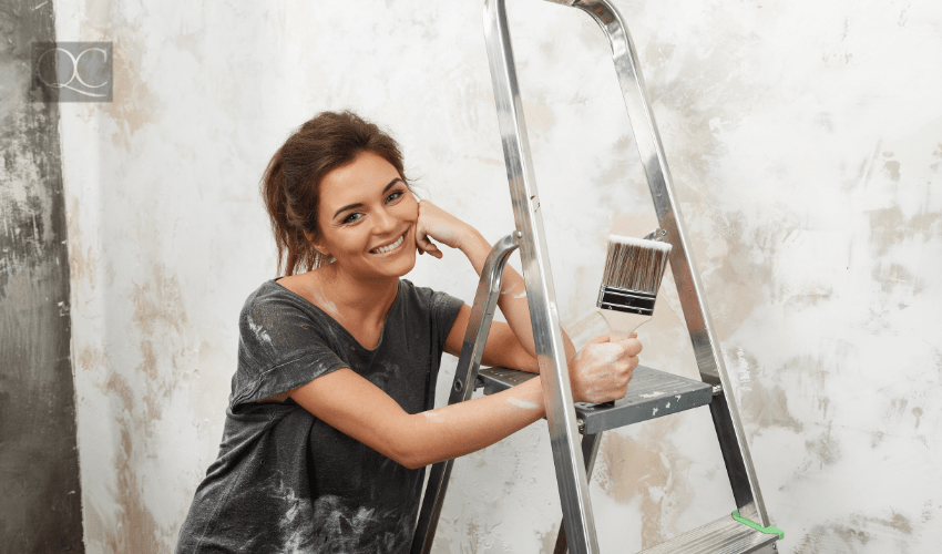 happy woman painting wall at home