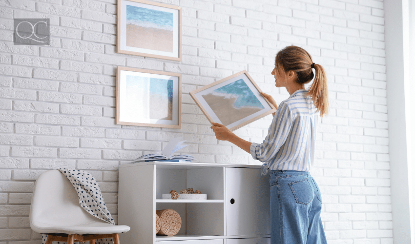 design course article, in-post image, woman hanging up artwork on wall at home