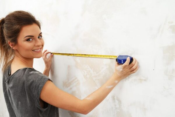 How to become an interior decorator measuring for beginners Feature Image, woman measuring wall with measuring tape