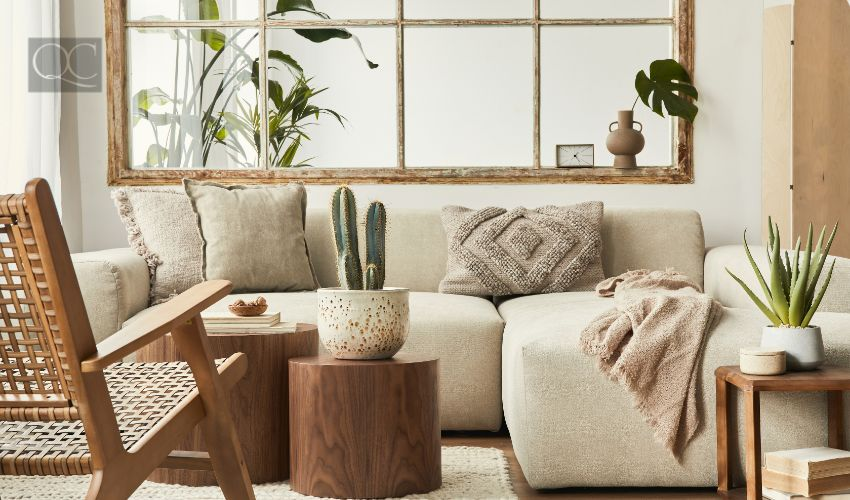 Interior design of living room with stylish modular beige sofa, wooden coffee tables, plants, pillows, plaid, neutral room divider, decoration and elegant accessories. Modern home decor