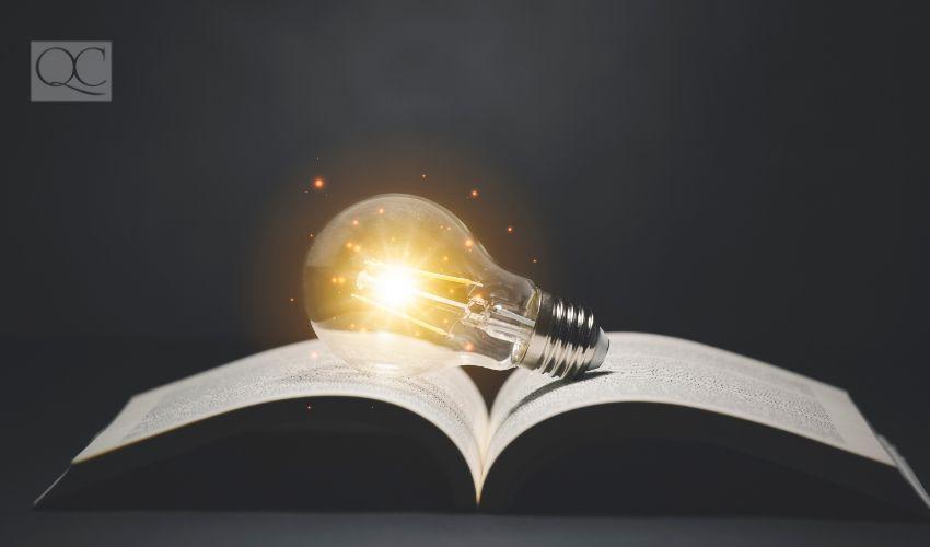 Light bulb and opened vintage book style vintage dark background