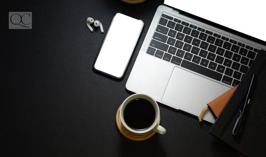 Top view of dark workspace with laptop, smartphone, coffee cup, stationery and copy space, clipping path