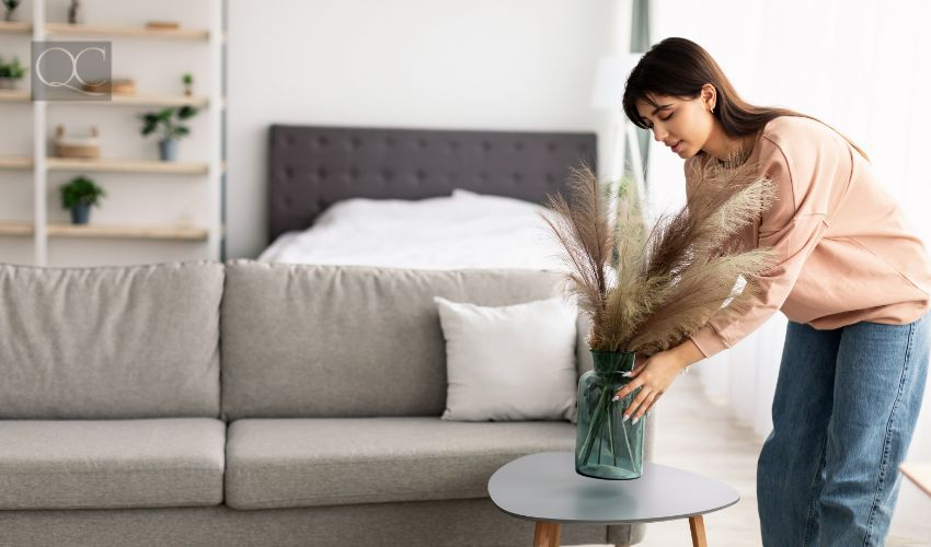 Casual young lady putting glass vase with dried flowers on tea table. Millennial woman decorating her modern apartment and bedroom or living room with pampas grass