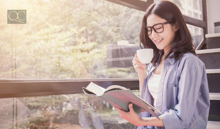 Woman drinking coffee and reading textbook