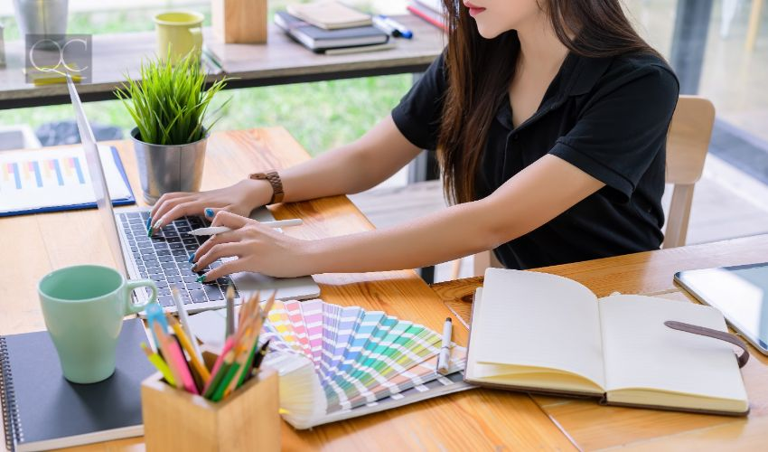 Color consultant certification in-post image, adult woman working on laptop at desk, with color swatches and notebook beside her