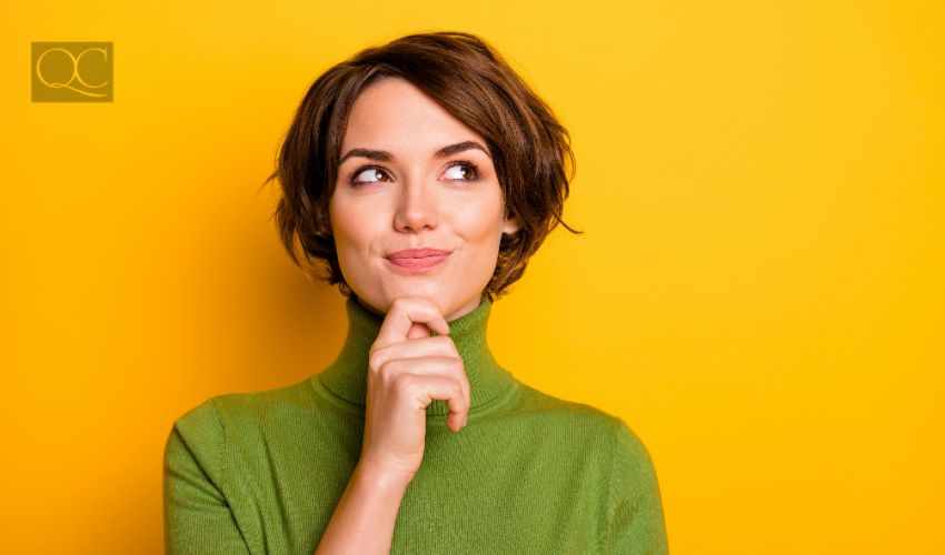 Adult woman thinking with a smile in front of yellow background