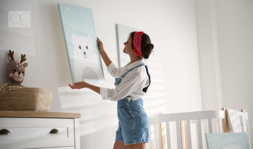 Interior decorator hanging up artwork in baby nursery