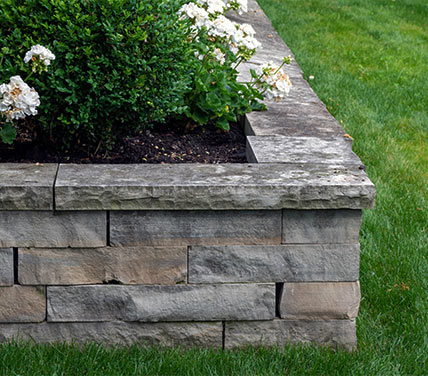 Stone hardscape surrounding garden bed